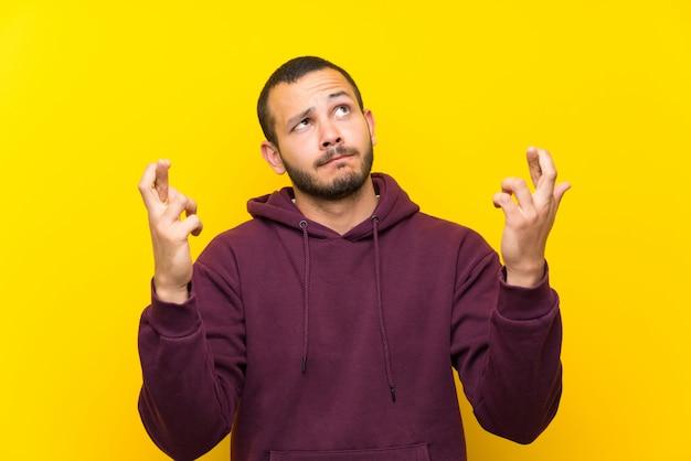 Kolumbijski mężczyzna z bluzą nad żółtą ścianą z palcami krzyżującymi i życzący najlepszy