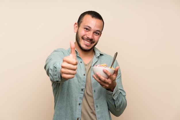 Kolumbijski mężczyzna z miską zbóż daje kciuk w górę gest i uśmiecha się