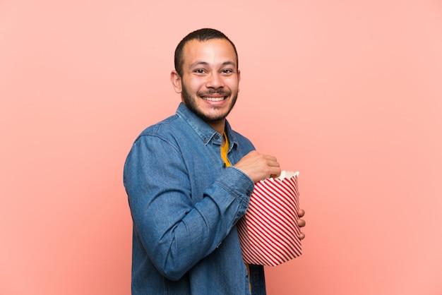 Kolumbijski mężczyzna z popcornsover odizolowywał menchii ścianę
