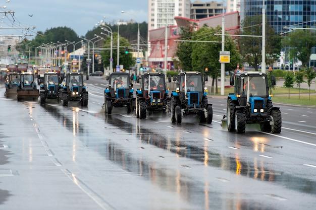 Kolumna ciągników czyści ulicę w ciepłym sezonie