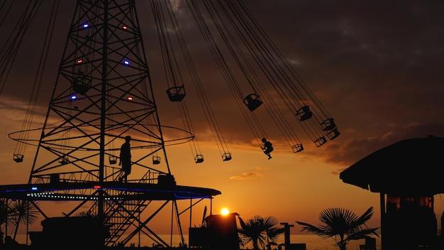 Kołysząca się karuzela karuzela przejażdżka łańcuchem o zachodzie słońca. rozrywka na plaży, sylwetki palm na tle nadmorskiego zachodu słońca