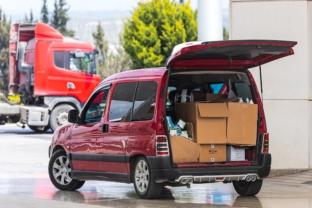 Kombi z otwartymi stanowiskami bagażowymi przygotowane do rozładunku skrzynek na parkingu