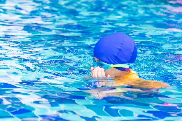 Kombinezon mokry azjatycki chłopiec z okularami pływać jest pływać w basenie