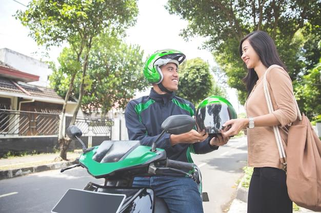 Komercyjny motocykl taksówkarz daje hełm jego klientowi