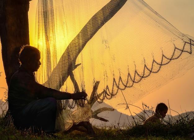 Komercyjny rybak naprawia jego sieci rybackie.