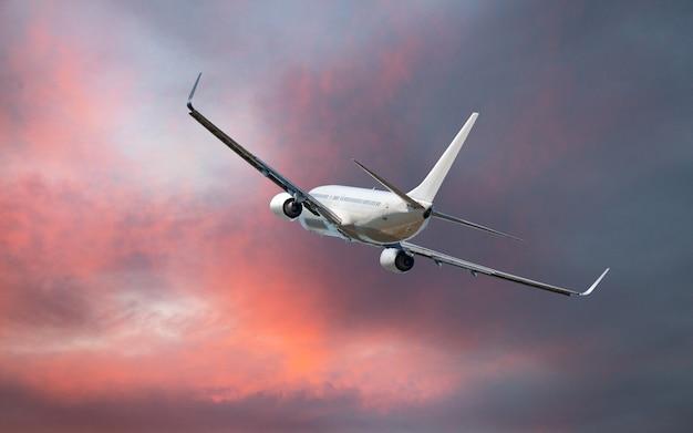 Komercyjny samolot lecący nad chmurami w dramatycznym świetle zachodu słońca