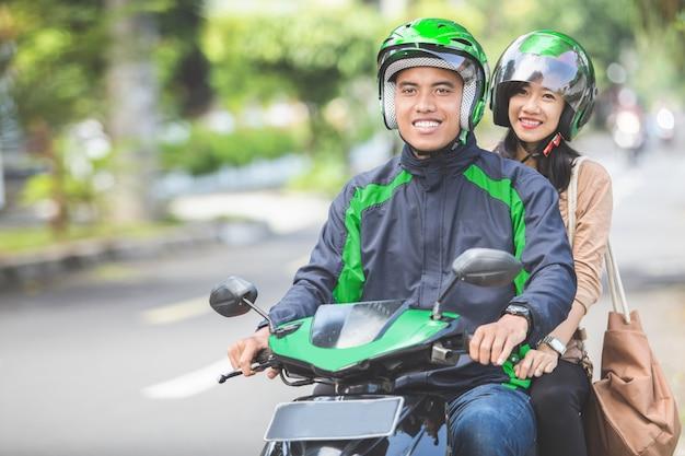 Komercyjny taksówkarz motocyklowy zabiera swojego pasażera do miejsca docelowego