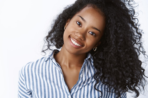 Komestologia, pielęgnacja skóry, koncepcja stylu życia. beztroska młoda ciemnoskóra kobieta pochyla głowę radośnie uśmiechając się białymi zębami pokazując piękne mocne kręcone włosy zachwycona idealną skórą stosując produkty spa