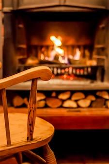 Komfort domu. kołysząc krzesło przy kominku. zdjęcie wnętrze pokoju. krzesło obrotowe w salonie z urządzonym nowoczesnym kominkiem