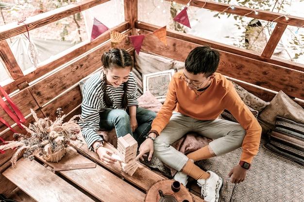 Komfortowe miejsce. zadowolony brunet krzyżuje nogi podczas odpoczynku ze swoją dziewczyną