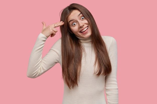 Komiczna piękna młoda kobieta z radosnym wyrazem twarzy, trzyma palce na skroniach, udaje, że robi gest samobójczy, ubrana niedbale