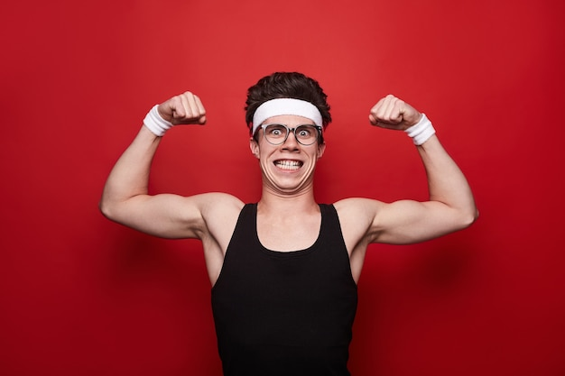 Komiks męski nerd w okularach pokazujący bicepsy i patrzący na kamerę na czerwonym tle w studio