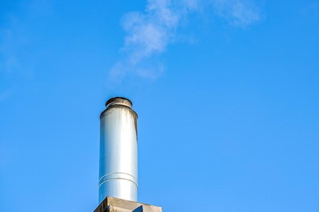 Komin z wznoszącym się dymem na tle błękitnego nieba. ogrzewanie domu w zimie. komin ze stali nierdzewnej z unoszącym się dymem.