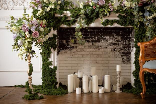 Kominek i świece. obszar weselny. vintage kominek ozdobiony wiosennymi kwiatami, wieniec, świece. ściana z cegły.