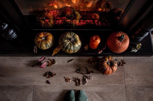 Kominek ozdobiony dyniami i suchymi jesiennymi liśćmi oraz pomarańczową świecą. przytulny dom koncepcja. przygotowanie do halloween.