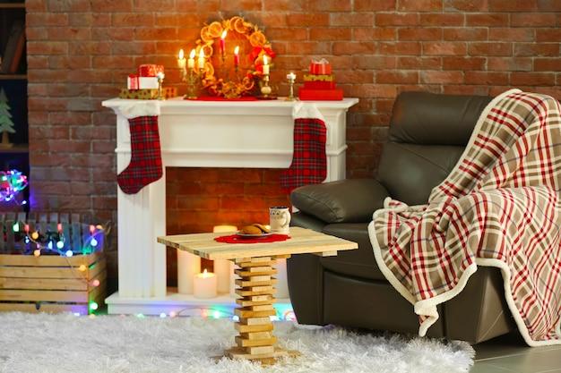 Kominek z pięknymi dekoracjami świątecznymi w wygodnym salonie