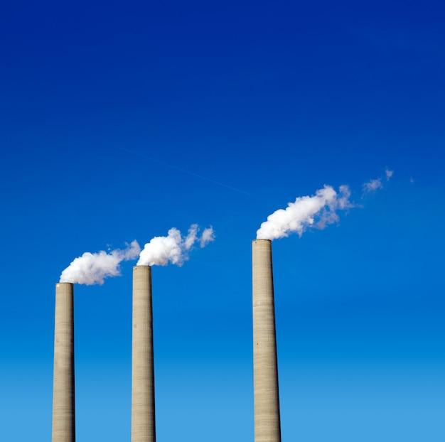 Kominowy bielu dym trzy z rzędu na niebieskim niebie