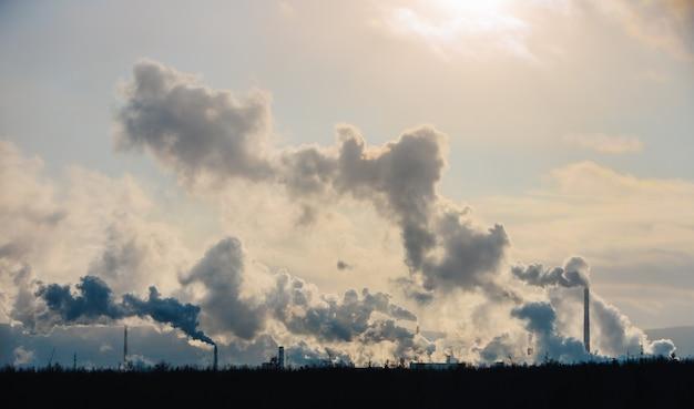Kominy fabryczne zanieczyszczają atmosferę gęstym dymem.