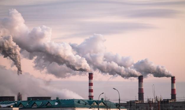 Kominy przemysłowe z dużym dymem powodujące zanieczyszczenie powietrza jako problem ekologiczny na różowym niebie o zachodzie słońca