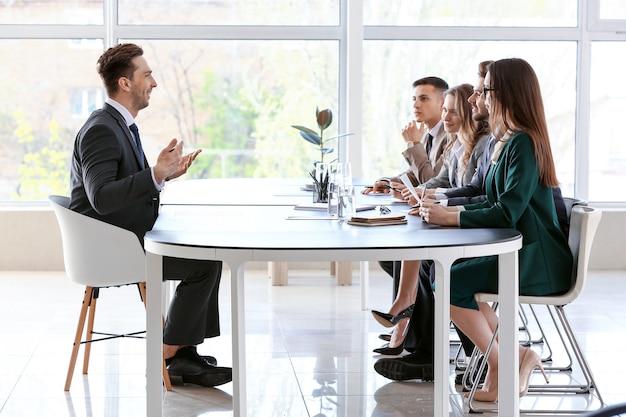 Komisja ds. zasobów ludzkich przeprowadza rozmowę kwalifikacyjną z mężczyzną w biurze