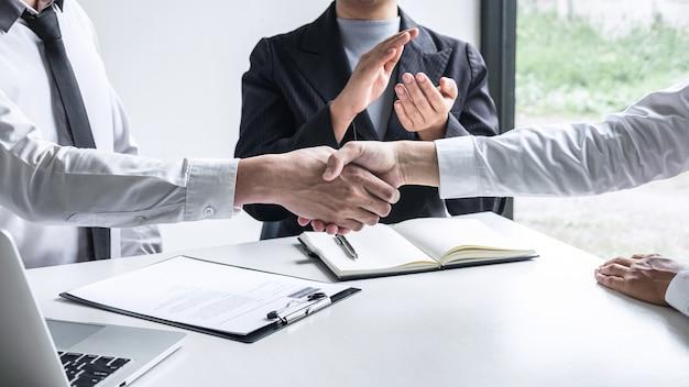 Komitet i nowy pracownik ściskają sobie ręce po dobrym interesie