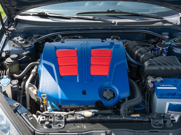 Komora pojazdu z otwartą maską samochodu z silnikiem pokryta błyszczącą plastikową osłoną