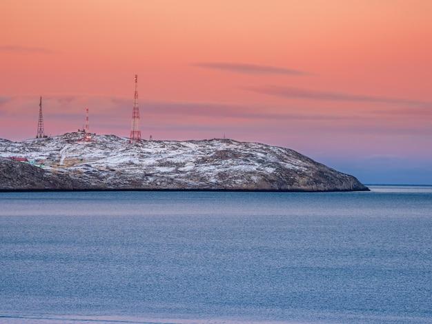 Komórka wieże na pokrytych śniegiem wzgórzach w tundrze. piękny zachód słońca pagórkowaty krajobraz arktyki. półwysep kolski.