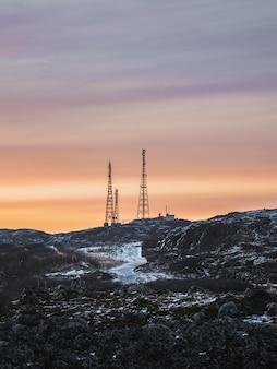 Komórka wieże na pokrytych śniegiem wzgórzach w tundrze. piękny zachód słońca pagórkowaty krajobraz arktyki