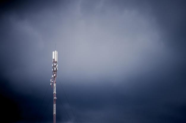 Komórkowa stacja bazowa, antena przekazu sygnału na tle ciemnego burzowego nieba