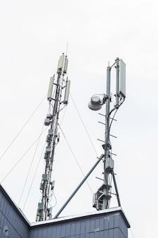 Komórkowe anteny telefonu komórkowego na dachu budynku. technologia telekomunikacyjna gsm (5g, 4