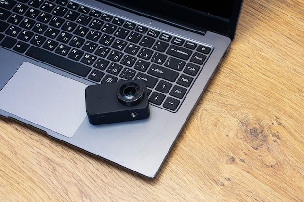 Kompaktowa kamera akcji na stole na tle laptopa.