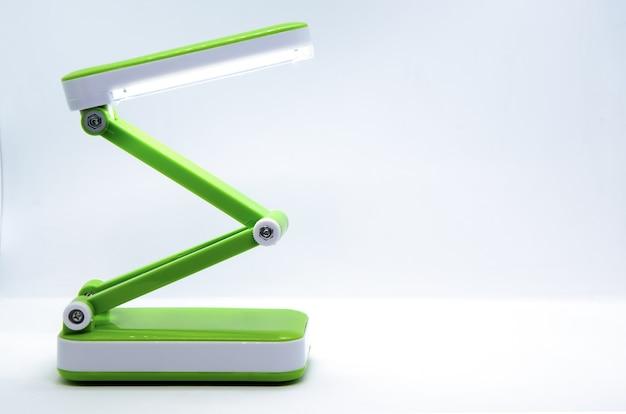 Kompaktowa składana przenośna lampa biurkowa led z elastycznym korpusem z jasnozielonego plastiku na białym tle.