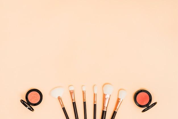 Kompaktowy puder do twarzy z białymi pędzlami do makijażu na kolorowym tle