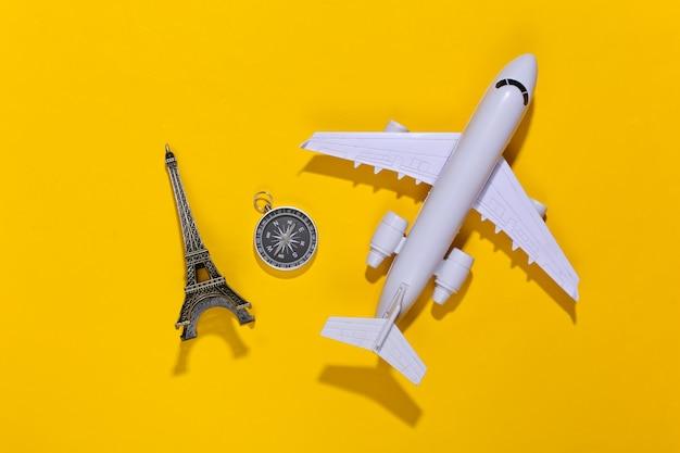Kompas, figurka wieży eiffla i samolot na jasnożółtym kolorze