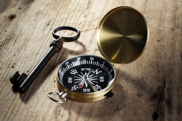 Kompas i antyczny klucz leżą na drewnianym