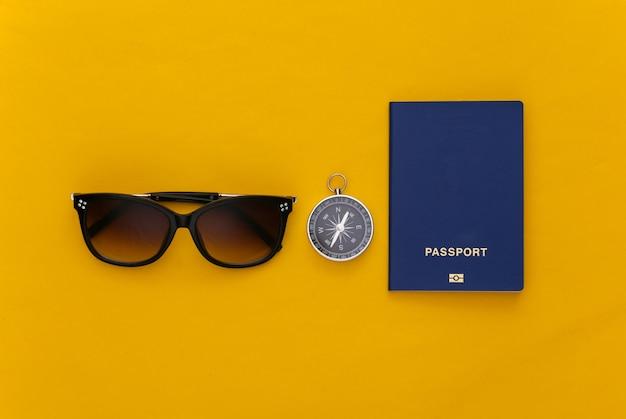 Kompas i okulary przeciwsłoneczne, paszport na żółtym tle. widok z góry. koncepcja podróży minimalizm. płaskie ułożenie