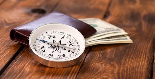 Kompas i portfel z dolarami amerykańskimi na drewnianym tle jako koncepcja biznesowa