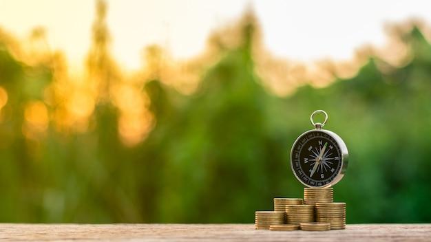 Kompas i złote monety na drewnianym biurku. - koncepcja kierunku gospodarczego.