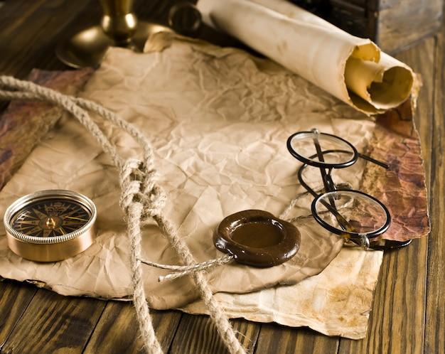 Kompas, lina i okulary na starym papierze