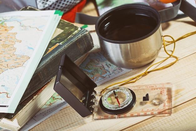 Kompas, mapa, kijki trekkingowe i plecak na drewnianym tle