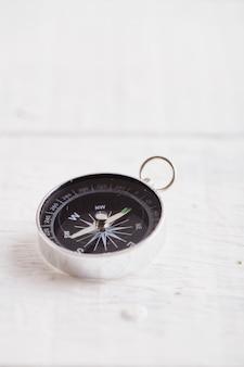 Kompas na białym drewnianym stole