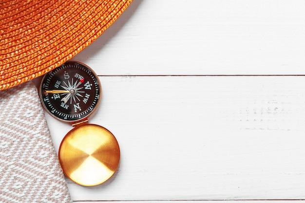 Kompas na białym drewnianym stołowym tle