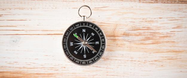 Kompas na drewnianej scenie z białym odcieniem