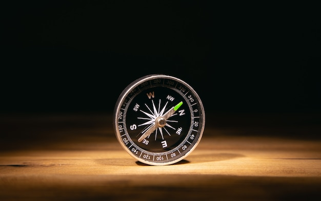 Kompas na stole na ciemnym tle