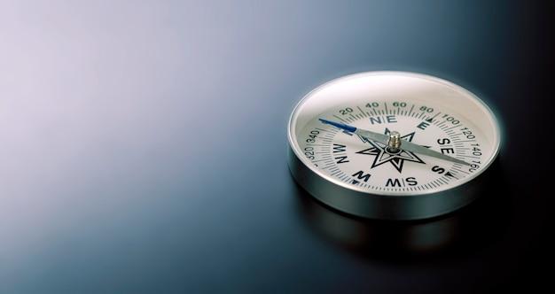 Kompas na tle czarnej tablicy i dużo miejsca na kopię. koncepcja - kompas wskazujący właściwy kierunek w biznesie, finansach, samorozwoju lub życiu duchowym. skopiuj miejsce.