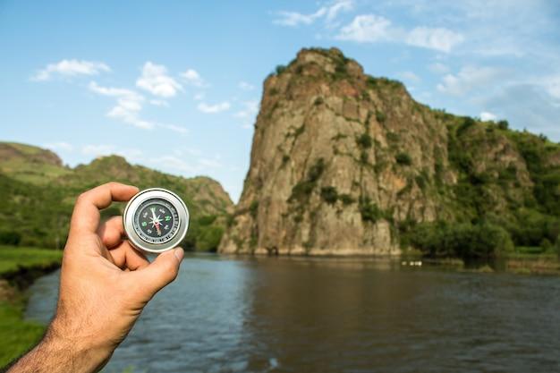 Kompas na tle rzeki i skał