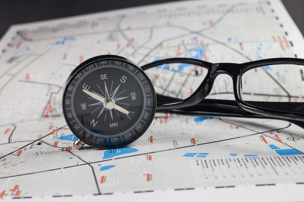 Kompas nawigacyjny obok mapy i okularów