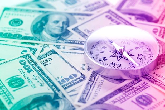 Kompas podróżny na tle dolarów amerykańskich w świetle neonowym