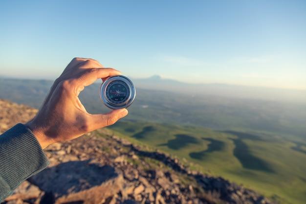 Kompas ręka człowieka w górach o zachodzie słońca