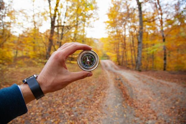 Kompas ręka człowieka w lesie jesienią